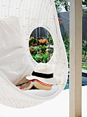 Sunhat and book in white, wicker hanging chair with cushions