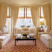 Luxuriously furnished interior with sofa set and coffee table on patterned rug in front of bay window with draped curtains