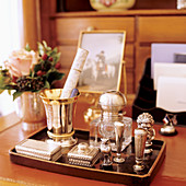 Silver caskets and ornaments on tray on desk