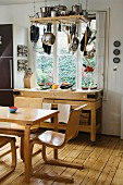 Dining area with Scandinavian-style wooden chairs and wooden table in front of workbench-style shelves below window; pots and pans hanging from ceiling rack
