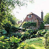 Summery garden and former mill converted into house with climber-covered facade