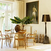 Delicate wooden chairs around modern table and potted banana tree in front of oil painting on wall