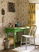A small green desk in the corner of a room with floral wallpaper
