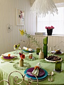 Table set with a green tablecloth in a white wood paneled dining room