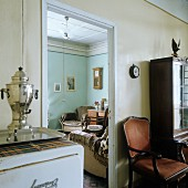 Open doorway with view into living room flanked by samovar on kitchen cupboard and antique armchair in dining room