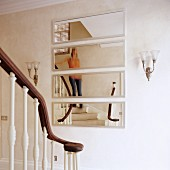 Stairwell with strip mirror and classic, English wooden staircase