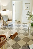 View from a staircase of a dog in an entrance hall with gray and white checkerboard stone floor and upholstered armchair with a floor lamp in a corner