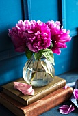 Pink peonies in a glass vase on antique books