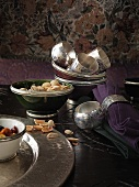 Silver serviette rings, serviettes and bowls with pistachios on a dark table