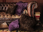 An old leather sofa with decorative cushions in brown and purple