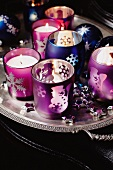 Glass candle holders and Christmas ornaments on a silver tray