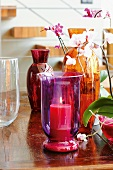 Colorful hurricane candle, glass vases and orchids on a table