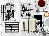 Schwarzweiss verpackte Geschenke, Notizbuch, Medaille, Kerze und eine Tasse Tee auf Holzuntergrung