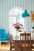 Dining table with wooden chairs and blue upholstered armchair in front of an arched window
