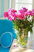 Peonies in a vase on a wooden table in front of an armchair