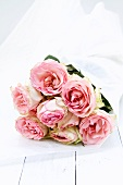 Bouquet of pink roses in silk paper on white painted wood boards