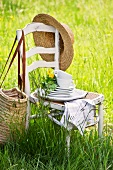 Stacked plates and cups with flowers on a wooden chair in a spring meadow, with a straw hat and a bag hanging on the back of the chair