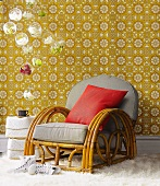Art Deco rattan chair in front of vintage floral wallpaper and hanging glass balls with orchid flowers