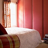 Bedroom with upholstered wardrobe doors, double bed with throw and window with patterned curtains