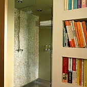 Green shower stall with mosaic tile wall and glass door next to a bookcase