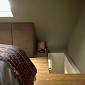 Attic bedroom with stairs, bed and skylight, green walls and wooden floor