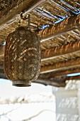 Oriental lantern below shady wooden pergola