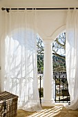 White curtains in front of masonry archways of loggia