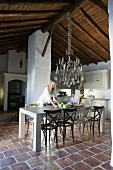 Rustic kitchen-dining room with chandelier hanging from original wooden roof structure