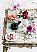 Boudoir accessories: roses in small vases and jewellery scattered on antique tray