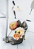 Roses of the varieties 'Cubana' and 'Félicité Parmentier' arranged in mesh high heels