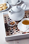 Teapot on woven newspaper table mat on tray