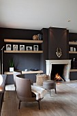 Classic modern armchairs with grey leather upholstery in front of open fireplace in black-painted wall in elegant living room
