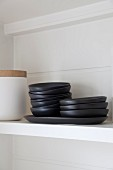 Black dishes on white shelf