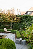 Garden with rustic wooden lounger on paved path and clipped hedges
