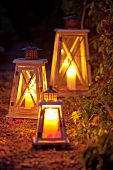 Lanterns with candles illuminating a garden path