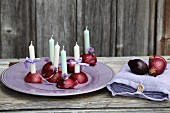 Halved red onions used as candlesticks and bag of linen napkins