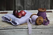 Red onions on linen bag next to wooden reels of purple and lilac lace ribbon