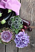 Globe thistles, hydrangeas and artichoke flower with aubergines, red onions and pale violet cloth on old board door