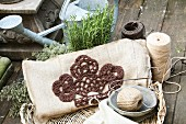 Embroidered cushion next to reels of yarn and herb plants in front of watering can