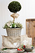 Cushion hand-crafted from hessian and painted with white paint in front of box lollipop tree in wicker planter