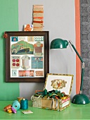 Framed vintage sewing supplies by a wall with a wide stripe; underneath several spools of thread and colorful ribbons in an old cigar box on a green lacquered table