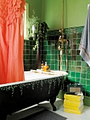 Green bathroom with freestanding, antique bathtub and fire engine red shower curtain with ruffles