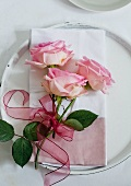 Three pink roses tied with ribbon on a cloth serviette on a charger