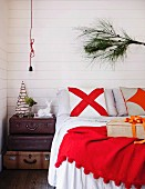 Pine branch as Christmas decoration in bedroom above double bed
