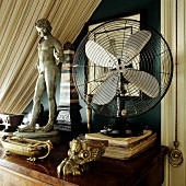 Brass ornaments and antique, miniature stone figurine next to fan on wooden table