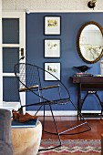 Black, vintage metal rocking chair against blue-painted wall in traditional living room