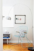 Pale blue, metal rocking chair and arc lamp in corner
