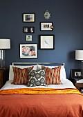 Doppelbett mit rotbrauner Tagesdecke und Kissen vor dunkel getönter Wand
