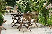 Wooden table and chairs in rose garden