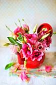 Zartes, kleines Blümensträußchen in rosa gehalten in einem roten Teekännchen arrangiert; einzelne Blütenblättchen liegen auf den gefalteten, blumigen Servietten auf dem weißen Untergrund